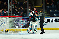 KELOWNA, CANADA - DECEMBER 1:  Kelowna Rockets' athletic therapist Scott Hoyer checks out goalie Roman Basran #30 on the ice after a collision in net against the Saskatoon Blades on December 1, 2018 at Prospera Place in Kelowna, British Columbia, Canada.  (Photo by Marissa Baecker/Shoot the Breeze)