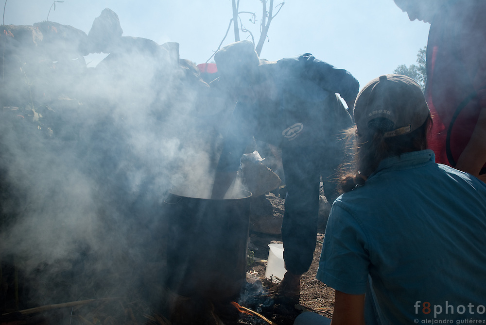 Women cooking the pork that has just been sacrificed.