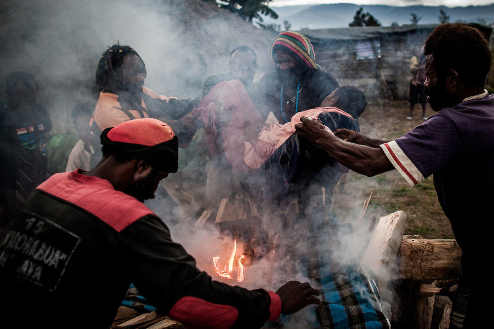 Dewi's lifeless body is carried onto the cremation pyre by her uncle.   <br />