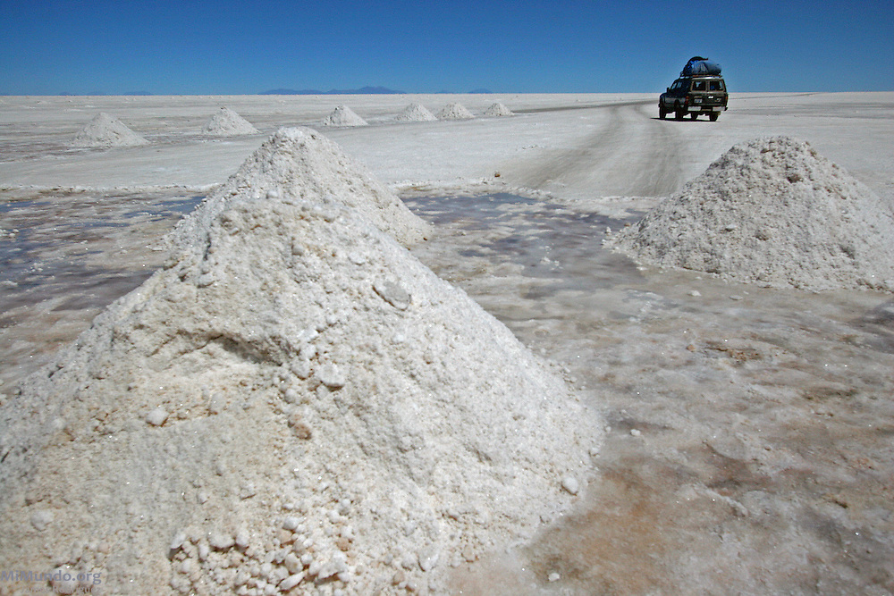An all-terrain vehicle drives past salt mining mounds on the Salar de Uyuni, the world's largest salt flat. The Salar de Uyuni sits at 3,600 meters above sea level and has a total surface area of 10,582 square kilometers.