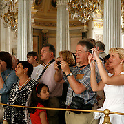 Visitors admire Catherine II's  Golden Peacock Clock acquired  in 1781 from England. The automaton clock has several moving parts including a peacock, a cockerel or rooster, an owl, a mushroom and a squirrel is on display at the Hermitage Museum.<br /> Photography by Jose More