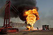 "Firefighters from the KWWK (Kuwait Wild Well Killers) attempt to kill an oil fire in the Rumaila field by guiding a ""stinger"" that will pump drilling mud into the damaged well. A ""stinger"" is a tapered pipe on the end of a long steel boom controlled by a bulldozer. Drilling mud, under high pressure, is pumped through the stinger into the well, stopping the flow of oil and gas. The Rumaila field is one of Iraq's biggest oil fields with five billion barrels in reserve. Rumaila is also spelled Rumeilah."
