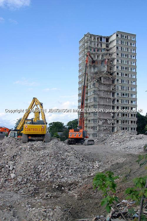 Demolition of high rise flats using a hydraulic jaw to cut through steel reinforced concrete.