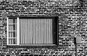 A window frame serves as counterpoint to a maze of bricks with varying textures & tones.  The diagonal lines and diamond shapes in the black security frame also contrast with the brick and window frame patterns. The image was finished to emulate Agfa APX 100 b&w  film.