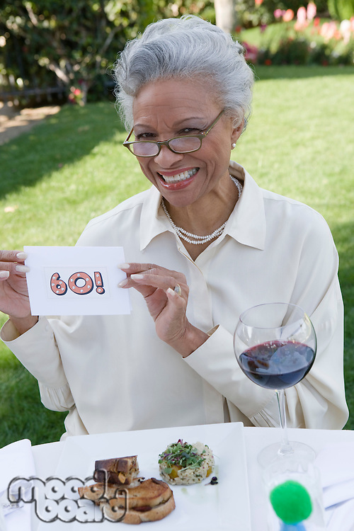 Senior woman holding piece of paper with her age written on it, smiling