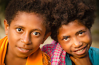 Two charming Papuan girls smile to camera in Lobo Village, Triton Bay, Papua, Indonesia. Travel photography by Djuna Ivereigh.