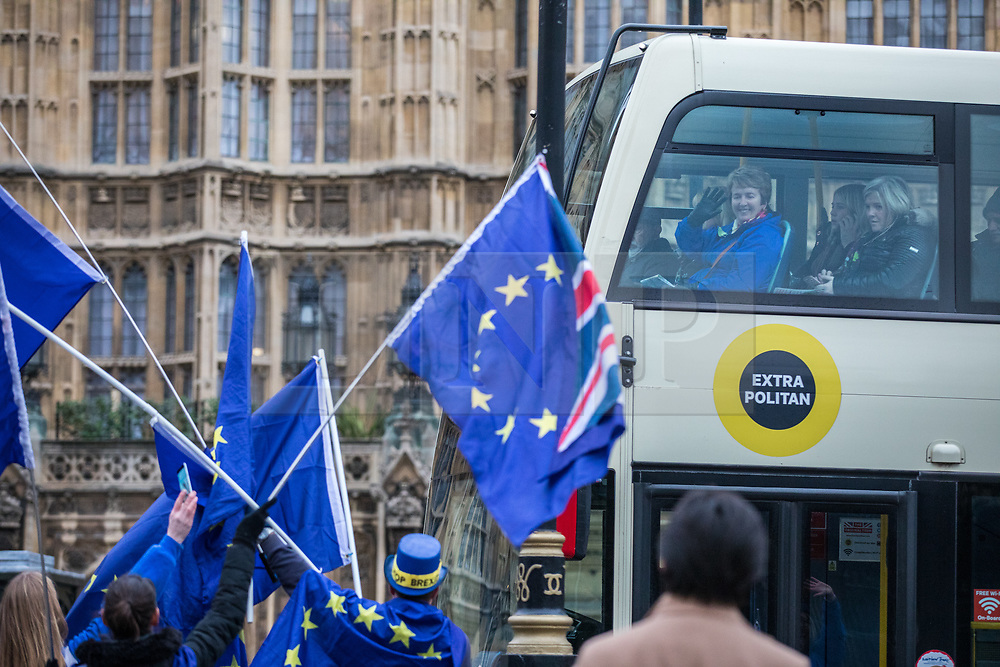 © Licensed to London News Pictures. 14/11/2017. London, UK. Tourists wave at anti-Brexit protesters demonstrating outside Parliament as MPs debate the European Union (Withdrawal) Bill. Photo credit: Rob Pinney/LNP