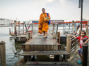 15 FEBRUARY 2015 - BANGKOK, THAILAND:  Buddhist monks disembark  at the pier at Wat Kalayanamitr, a large Buddhist temple in the Thonburi section of Bangkok next to the Catholic community of Santa Cruz. The temple was built in 1825, about 50 years after Santa Cruz Church was built.        PHOTO BY JACK KURTZ