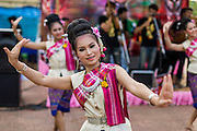 27 JUNE 2014 - DAN SAI, LOEI, THAILAND: A woman dances at one of the stages in Dan Sai during the Ghost Festival. Phi Ta Khon (also spelled Pee Ta Khon) is the Ghost Festival. Over three days, the town's residents invite protection from Phra U-pakut, the spirit that lives in the Mun River, which runs through Dan Sai. People in the town and surrounding villages wear costumes made of patchwork and ornate masks and are thought be ghosts who were awoken from the dead when Vessantra Jataka (one of the Buddhas) came out of the forest.    PHOTO BY JACK KURTZ