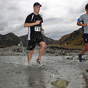 Runners Mark Hyland (left) and Steve Gould  cross Moke Creek on the Ben Lomond High Country Station during the Pure South Shotover Moonlight Mountain Marathon and trail runs. Moke Lake, Queenstown, New Zealand. 4th February 2012. Photo Tim Clayton