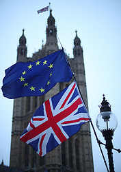 File photo dated 07/01/19 of EU and Union flags flying outside Parliament in Westminster, London, as Britain is unlikely to leave the European Union on March 29, the Economist Intelligence Unit has predicted.