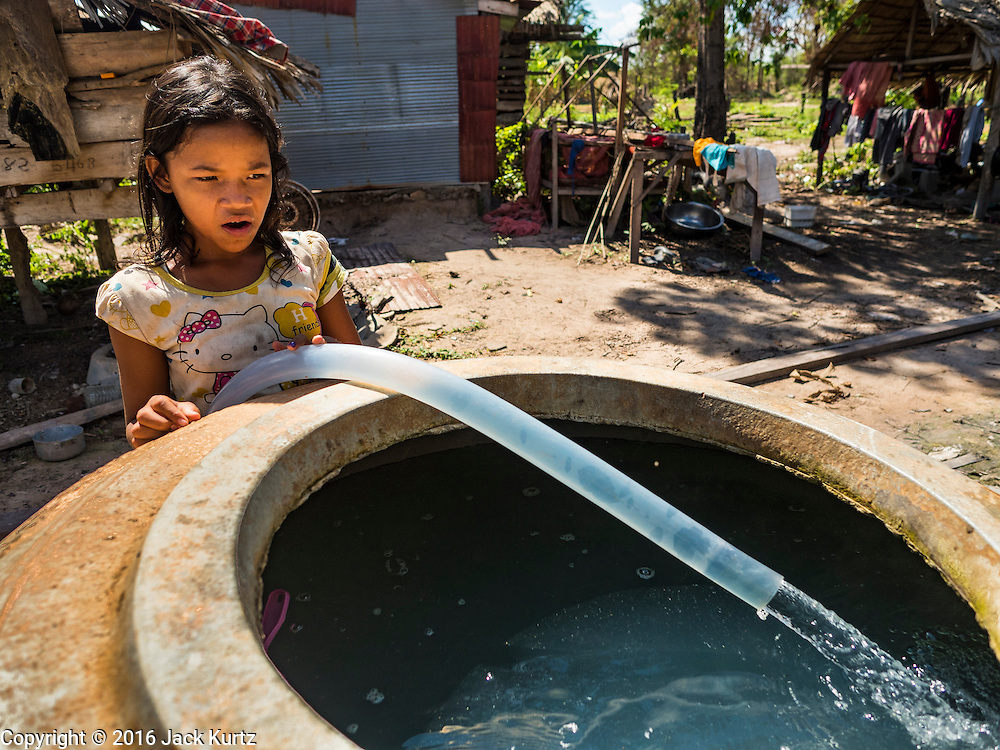02 JUNE 2016 - SIEM REAP, CAMBODIA: SREYOUN, 13 years old, stayed home from school to help fill her family's water jars. She handles her family's water needs and buys water from water sellers around her community. Her family is spending an extra $40 to $50 US per month on water, a large sum for a Cambodian family. The family raises pigs and chickens. Cambodia is in the second year of  a record shattering drought, brought on by climate change and the El Niño weather pattern. Farmers in the area say this is driest they have ever seen their fields. They said they are planting because they have no choice but if they rainy season doesn't come, or if it's like last year's very short rainy season they will lose their crops. Many of the wells in the area have run dry and people are being forced to buy water to meet their domestic needs.    PHOTO BY JACK KURTZ