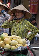 A street vendor wearing a traditional conical hat talking on her phone and selling fruit in the Old Quarter, Hanoi, Vietnam, Southeast Asia