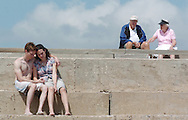 Keith Orsak and girlfriend Amanda Waguespack, both from Houston, sit along the sea wall while winter Texans Hoot Gibson and wife Jane Gibson from Austin, Minn., take in the sites on the beach on Padre Island in Corpus Christi.