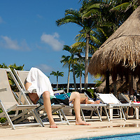 A man covers his face with a towel to avoid the sun.