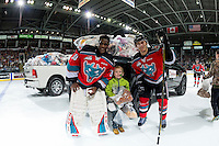 KELOWNA, CANADA - DECEMBER 3: Michael Herringer #30 and Jordan Borstmayer #11 of the Kelowna Rockets stand on the ice with a young fan after the annual teddy bear toss on December 3, 2016 at Prospera Place in Kelowna, British Columbia, Canada.  (Photo by Marissa Baecker/Shoot the Breeze)  *** Local Caption ***