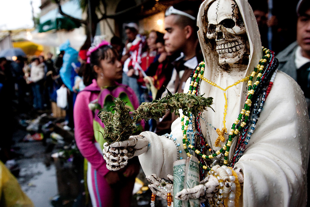 A Sante Muerte figure holds a marajuana bud at the Tipito shrine in Mexico City.