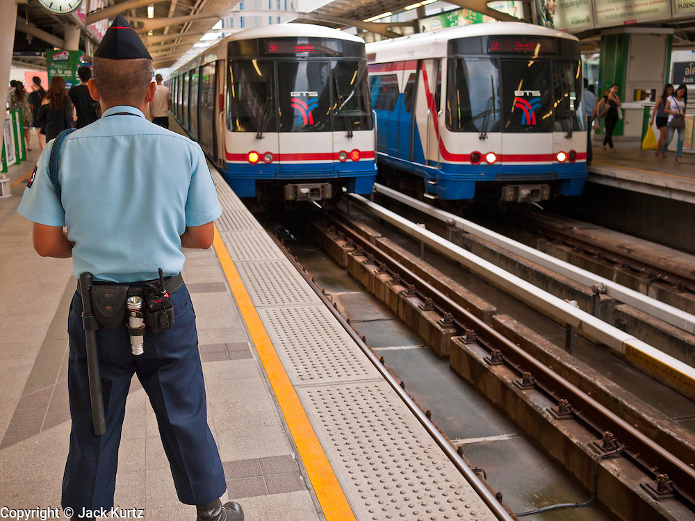 14 JULY 2011 - BANGKOK, THAILAND:   A security guard watches trains come and go in the Asoke station on the Sukhumvit line of the BTS Skytrain in Bangkok. The Bangkok Mass Transit System, commonly known as the BTS Skytrain, is an elevated rapid transit system in Bangkok, Thailand. It is operated by Bangkok Mass Transit System Public Company Limited (BTSC) under a concession granted by the Bangkok Metropolitan Administration (BMA). The system consists of twenty-three stations along two lines: the Sukhumvit line running northwards and eastwards, terminating at Mo Chit and On Nut respectively, and the Silom line which plies Silom and Sathon Roads, the Central Business District of Bangkok, terminating at the National Stadium and Wongwian Yai. The lines interchange at Siam Station and have a combined route distance of 55 km.   PHOTO BY JACK KURTZ