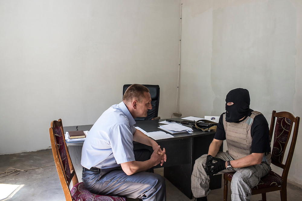 NOVODONETSKE, UKRAINE - MAY 21:   A member of the Donbass Battalion, a pro-Ukraine militia, meets with Mayor Aksionov Andrey Anatolievich (L) to ensure the integrity of the upcoming presidential election on May 21, 2014 in Novodonetske, Ukraine. Days before presidential elections are scheduled, questions remain whether the eastern regions of Donetsk and Luhansk are stable enough to administer the vote. (Photo by Brendan Hoffman/Getty Images) *** Local Caption ***