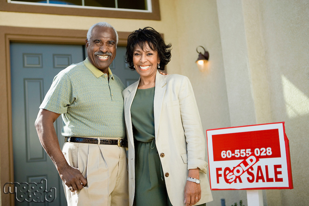 Middle-aged couple standing in front of new home portrait