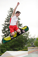 Goshen, NY - A member of the Skyriders, an acrobatic trampoline team, jumps high into the air on a snowboard at the Great American Weekend festival on July 5, 2008.