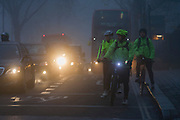 Commuting cyclists wait to cross a junction at dawn on a foggy morning in south London.