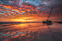 """A beached sailboat witnesses vibrant sunrise colors reflecting into the wet sands along Cape Hatteras National Seashore, North Carolina.  The Outer Banks have been historically dubbed """"The Graveyard of The Atlantic"""" because of the shoaling offshore as a result of the dueling Gulf and Labrador currents."""