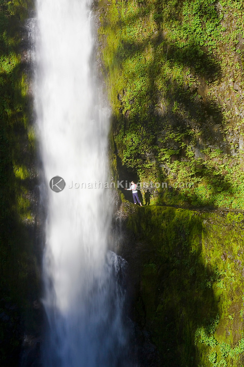 A young woman, catches water drops in her hands from the beautiful Tunnel Falls on Eagle Creek trail in the Columbia River Gorge, Oregon, USA.  Tunnel Falls received its name due to a tunnel being cut from the bedrock behind the falls so that hikers and trail runners can pass further up the gorge.  The trail becomes very narrow during this section and it is necessary to hold onto a safety cable. (Model Released)