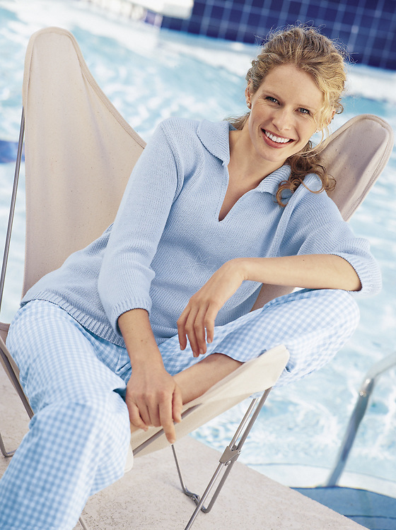 Jane is relaxing at her pool while being photographed in her light blue top with checkered pants for a fashion catalog.