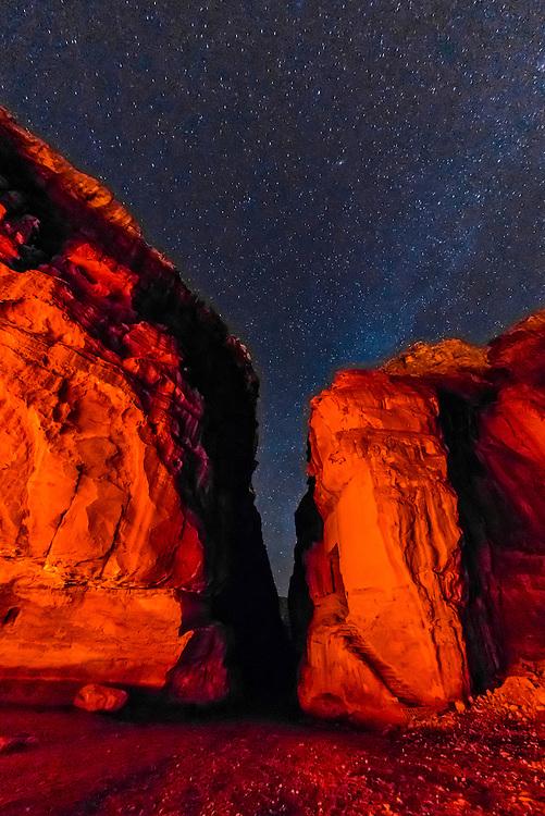 A starry sky over rock formations at night, Petra Archaeological Park, Petra, Jordan.