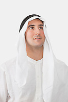 Arab businessman looking away against white background