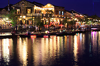 Tourist boats ply the Thu Bon River in front of Bach Dang Street in the old town of Hoi An, Vietnam
