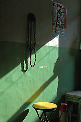 China, Taiyuan, 2007. A minimalist scene in an old woman's home, as afternoon sunlight illuminates her beliefs..