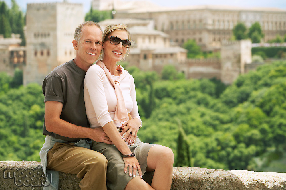 Tourist Couple sitting on Wall in Granada Spain portrait