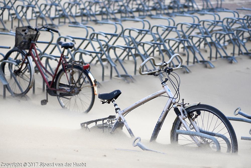 Fiets in fietsenrek tijdens storm  verdwijnt langzaam onder het zand - Cycle in bicycle rack during stormy weather disapears slowly under a sand dune