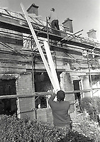 Roman Catholics are rebuilding and making habitable again houses at Farringdon Gardens, Ardoyne, Belfast, which were evacuated and in many cases set on fire by fleeing Protestants who left the area following post-Internment rioting. Date that photos were taken is uncertain but probably 3 or 4 months after the rioting in August 1971. 426/71, 197111000426c.<br />