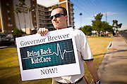 Oct. 4, 2010 - PHOENIX, AZ: MATT JEWETT, from Phoenix, AZ, a supporter of Kids Care, the Arizona medical insurance program for children, pickets the front of Maricopa Medical Center during an appearance by Arizona Gov. Jan Brewer Monday. Gov. Brewer is running for reelection and appears headed to an easy win. Since signing Arizona's tough immigration bill, SB 1070, and cutting budgets for some of Arizona's social services, like health care for children, her popularity has soared. Her reelection campaign has been dogged by protests from education, health care and immigration advocates but she doesn't engage them and continues to be popular in pre-election polling.    Photo by Jack Kurtz