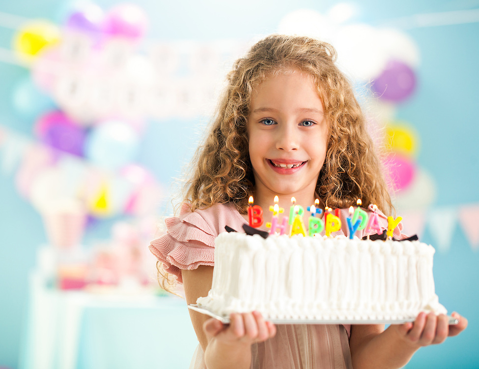 Cute smiling girl holding a birthday cake.