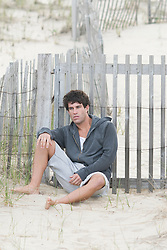 Young man sitting against a wooden fence in the sand at the beach