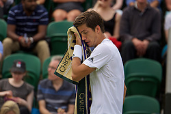 LONDON, ENGLAND - Tuesday, June 28, 2016: Aljaz Bedene (GBR) wipes his face with a Wimbledon towel during the Gentlemen's Singles 1st Round match on day two of the Wimbledon Lawn Tennis Championships at the All England Lawn Tennis and Croquet Club. (Pic by Kirsten Holst/Propaganda)