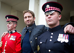 © Licensed to London News Pictures. 04/04/2013. London, UK Hollywood actor Gerard Butler poses with  Sergeant (Sgt) Alan Duff (28) and Sergeant (Sgt) John Norwood of F Company the Scots Guards.  Butler met the soldiers at Wellington Barracks in Central London ahead of a special preview screening of Hollywood movie Olympus Has Fallen, released 17th April 2013. ..The actors spent time talking to the soldiers prior to the troops watching a special preview of the film in the barracks. Photo credit : Alison Baskerville/LNP
