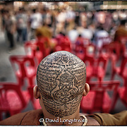 "In this ""Signature Series"" image by David Longstreath, a young Buddhist Monk displays his tattoos at the annual tattoo festival at Wat Bang Pra in Chong Nasi, Thailand."