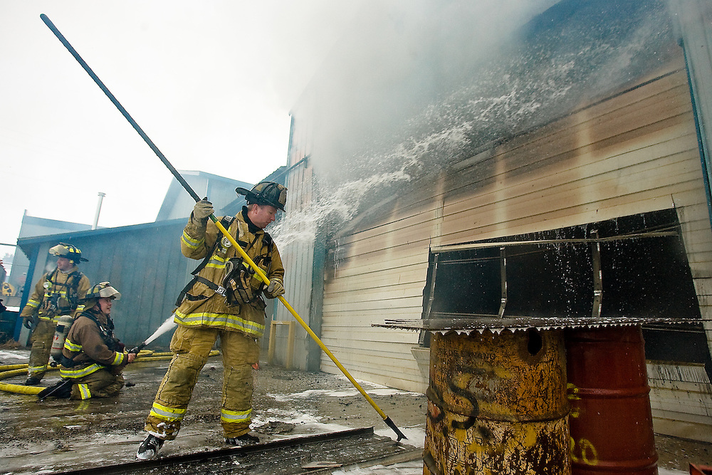 JEROME A. POLLOS/Press..Coeur d'Alene firefighter Jeff Sells clears debris from the scene of a fire at Ground Force Manufacturing shortly after noon today. The initial damage is estimated at costing more than $700,000. One employee of Ground Force was taken to the hospital for smoke inhalation.