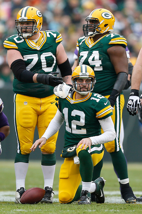GREEN BAY, WI - DECEMBER 2:  Aaron Rodgers #12 is helped up by T.J. Lang #70 of the Green Bay Packers after being sacked during a game against the Minnesota Vikings at Lambeau Field on December 2, 2012 in Green Bay, Wisconsin.  The Packers defeated the Vikings 23-14.  (Photo by Wesley Hitt/Getty Images) *** Local Caption *** Aaron Rodgers; T.J. Lang