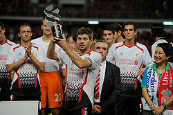 BANGKOK, THAILAND - Sunday, July 28, 2013: Liverpool's captain Steven Gerrard lifts the Standard Chartered trophy, the fourth in four games, after a preseason friendly match against Thailand XI at the Rajamangala National Stadium. (Pic by David Rawcliffe/Propaganda)