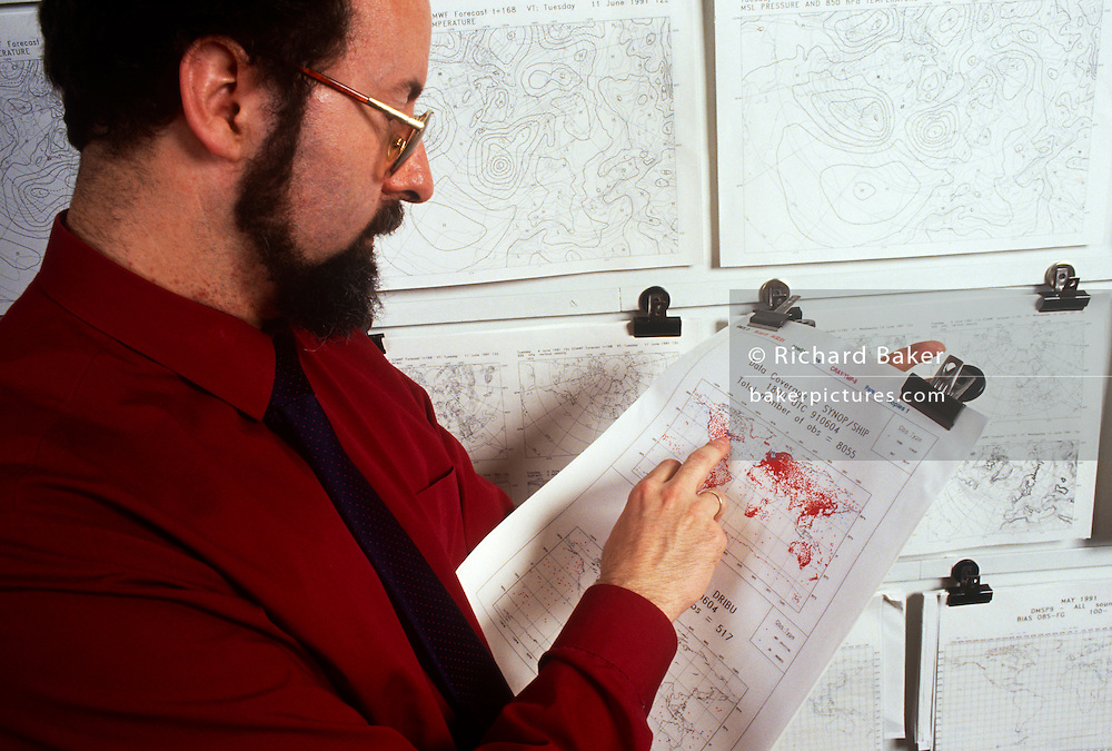 "An employee with 1990s weather chart technology at the European Centre for Medium-Range Weather Forecasts (ECMWF), Reading, UK. ECMWF is an international organisation supported by 31 States, its role is ""to provide monthly and seasonal-to-interannual forecasts; to deliver real-time analyses and forecasts of atmospheric composition; to carry out climate monitoring through regular re-analyses of the Earth-system and to contribute towards the optimization of the Global Observing System."""