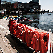 A rack of personal flotation devices, PFDs, line the dock in the Baltimore Harbor, MD. The Baltimore aquarium is in the background.