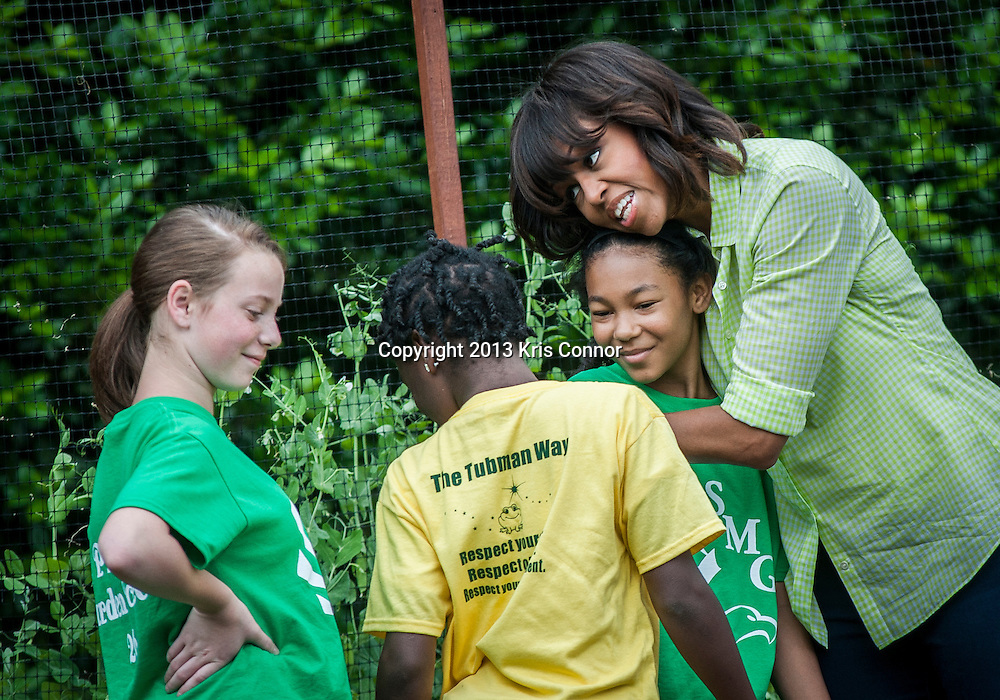(L-R) Rachel Bradley and Kyla Bourne of Sarah Moore Greene Magnet Technology Academy School, Knox County, TN  hug the First Lady Michelle Obama during an event where they harvested the White House Kitchen Garden for the fifth year in a row at the White House on May 28, 2013 in Washington DC. Photo by Kris Connor