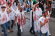 Shiite muslims, covered in their own blood, carrying swords and knives, marching through the streets of Nabatieh, Lebanon, commemorating the Day of Ashura (November 14, 2013).