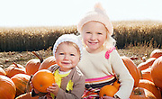 Portrait of sisters with pumpkin sitting on farm
